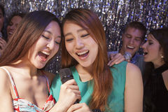Group of friends singing into a microphone at karaoke Stock Images
