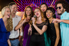 Group of friends singing song together in bar. Group of happy friends singing song together in bar Stock Photos