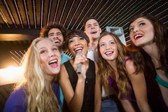 Group of friends singing song together in bar. Group of happy friends singing song together in bar royalty free stock images