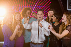 Group of friends singing song together in bar. Group of happy friends singing song together while having glass of champagne in bar Royalty Free Stock Photos