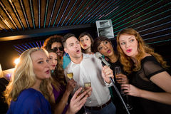 Group of friends singing song together in bar. Group of happy friends singing song together while having glass of champagne in bar Stock Photography