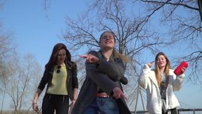 Group of friends sings and dances at the street in park. Funny friends sings and dances at the street in park. Teenagers have fun together and moving to the beat stock video