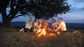 Group of friends sit next to a campfire with warm drinks and talk