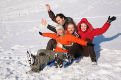 Group of friends sit on plastic sled Royalty Free Stock Photo