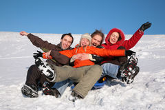 Group of friends sit on plastic sled Stock Photos