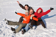 Group of friends sit on plastic sled Stock Photo