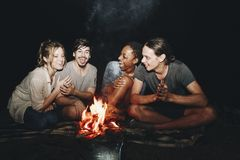 Group of friends sitting around a bonfire at a campsite stock images