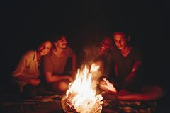 Group of friends sitting around a bonfire at a campsite royalty free stock image