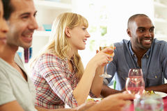 Group Of Friends Sitting Around Table Having Dinner Party Stock Photo