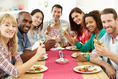 Group Of Friends Sitting Around Table Having Dinner Party. Smiling To Camera Holding Glass Of White Wine Stock Photos