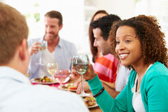 Group Of Friends Sitting Around Table Having Dinner Party. Talking To Each Other Stock Photos