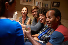 Group of friends sitting around a table at house party stock photo