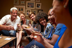 Group of friends sitting around a table at house party stock image