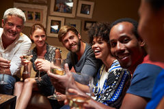 Group of friends sitting around a table at house party royalty free stock photo