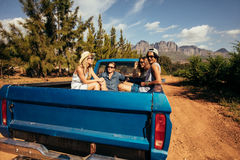 Group of friends sitting at the back of a pick up car Royalty Free Stock Photo