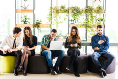 Group of friends sitting on chairs near each other and everyone is busy in his divices in modern office room. Together fun in devi Royalty Free Stock Images