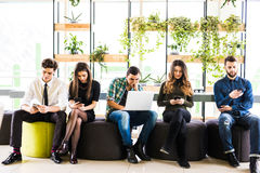 Group of friends sitting on chairs near each other and everyone use his divices in modern office room. Together fun in device. Stock Photo