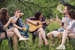 Group of friends sitting in circle out in park. Group of friends hanging out in park. Friends having calm time in park sitting in circle playing some guitar stock images