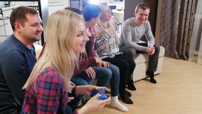 Group of friends sitting on the couch and gaming. Cheerful company plays video games stock footage