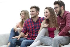 Young friends sitting on the couch and rooting for their favorite team. Group of friends sitting on the couch and rooting for their favorite team Royalty Free Stock Photography