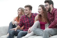 Young friends sitting on the couch and rooting for their favorite team. Group of friends sitting on the couch and rooting for their favorite team Stock Photo