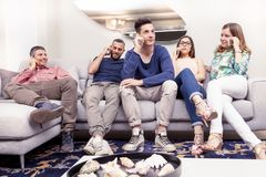 Group of friends on the couch to the phone at the same time. Group of friends sitting on the couch to the phone at the same time  in a modern apartment Royalty Free Stock Photography