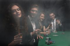 Group of friends sitting at game table in casino. Photo with copy space Stock Images