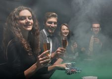 Group of friends sitting at game table in casino. Photo with copy space Royalty Free Stock Photography