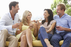 Group Of Friends Sitting On Outdoor Seat Together Stock Photos