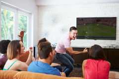Group Of Friends Sitting On Sofa Watching Soccer Together Royalty Free Stock Photos