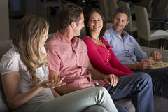 Group Of Friends Sitting On Sofa Watching TV Together Stock Photo