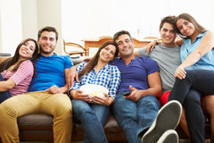 Group Of Friends Sitting On Sofa Watching TV Together Stock Photography