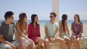 Group of friends sitting on stone wall near beach stock footage