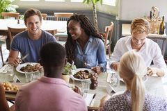 Group Of Friends Sitting At Table In Restaurant Enjoying Meal Together royalty free stock photo