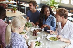 Group Of Friends Sitting At Table In Restaurant Enjoying Meal Together stock photography