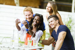 A group of friends sitting a table and talking smiling  while ta Royalty Free Stock Photography