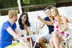 A group of friends sitting a table and talking smiling  while ta Royalty Free Stock Image