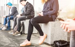 Group of friends sitting and using smartphone at university college. Backyard break - Guys and girls addicted by mobile smart phone - Technology concept with royalty free stock photos