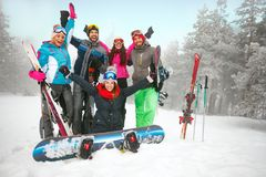 Group of friends skiers and snowboarders having fun on snowbound. Group of cheerful friends skiers and snowboarders having fun on snowbound winter forest Royalty Free Stock Photo