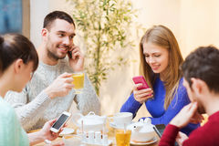 Group of friends with smartphones meeting at cafe. People, leisure, friendship and technology concept - group of happy friends with smartphones meeting at cafe Stock Photo