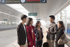 Group of friends smiling and talking on railway platform Royalty Free Stock Photos
