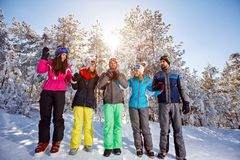 Group of friends on snow in forest stock photo