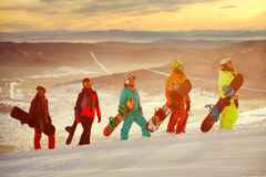 Group of friends snowboarders having fun on the top of mountain Royalty Free Stock Images