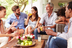 Group of friends socialising in a conservatory Royalty Free Stock Image