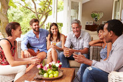 Group of friends socialising in a conservatory Royalty Free Stock Images