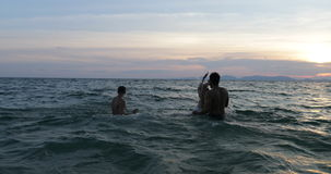 Group Of Friends Splashing In Sea At Sunset, Cheerful People Young Swimming On Beach Together During Summer Vacation stock footage