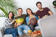 Group of friends sport fans watching basketball game looking camera. Young women and men watching tv basketball match together holding bowls with snacks looking Royalty Free Stock Images