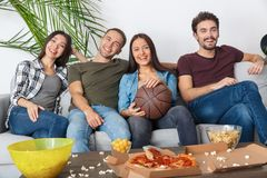 Group of friends sport fans watching basketball game time together. Young women and men watching tv basketball match smiling happy time together Royalty Free Stock Images