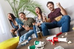 Group of friends sport fans watching football match cheering team Stock Images