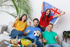 Group of friends sport fans watching match in colorful shirts girl holding new zealand flag royalty free stock images